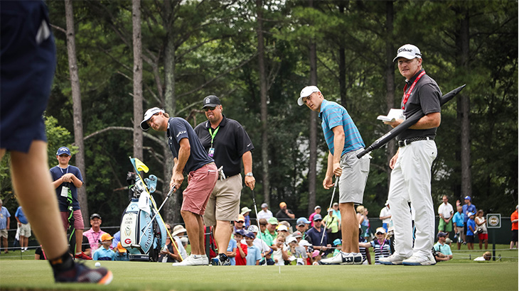 Kisner and Spieth watch their putts roll on the...